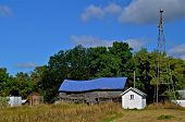 Dilapidated barn with a blue roof