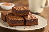 foto of brownie  - Freshly baked brownie pieces on a plate with cup in the back (Selective Focus Focus on the left front part of the upper brownie)