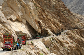 stock photo of skardu  - Big tracks waiting for the road to be cleared of debris after landslide Pakistan Road to Skardu - JPG