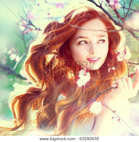 Spring beauty girl with long red blowing hair outdoors. Blooming trees. Romantic young woman portrai poster