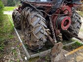 stock photo of mountain chain  - Closeup of wheels of the tractor chain forest in the mountains - JPG