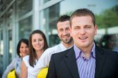 Engineer posing with coworkers in row in front of building