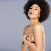 Upper body portrait of a beautiful nude African American woman protecting her breast with her hand p