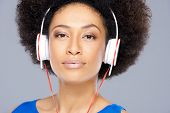 Trendy attractive young African American woman listening to music on a set of headphones isolated on