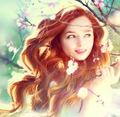 picture of blowing  - Spring beauty girl with long red blowing hair outdoors - JPG