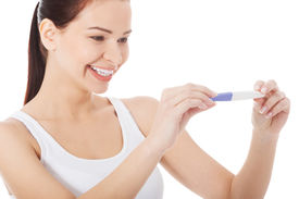 foto of teen pregnancy  - Happy smiling woman with pregnancy test - JPG