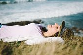 stock photo of rest-in-peace  - Funky young woman resting and relaxing towards the sea - JPG