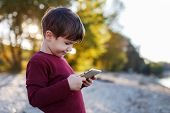 picture of angry bird  - Little boy playing on tablet outdoor portrait  - JPG