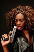 stock photo of gangsta  - A young beautiful african american female holds a semi automatic pistol during this dark photo shoot against black - JPG