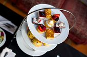 stock photo of three tier  - Afternoon tea on a three tiered plate - JPG