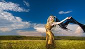 image of arabian  - Lovely young lady posing dramatically with long black veil on green field - JPG