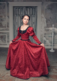 picture of pompous  - Young beautiful medieval woman in long red dress in the old room - JPG
