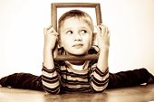 image of mischief  - Portrait of little funny blonde boy child holding photo frame framing his face looking into the corner studio shot - JPG