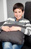 stock photo of preteen  - Smiling preteen on the sofa at home resting - JPG