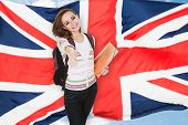 picture of citizenship  - Young Female Student Gesturing Thumb Up In Front Of British Flag - JPG
