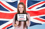 pic of citizenship  - Young Woman Holding Digital Tablet Asking Do You Speak English In Front Of British Flag - JPG