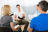 stock photo of scriptures  - Man Explaining To His Friends From Scripture - JPG