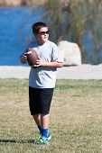 picture of pre-teen boy  - A pre-teen boy plays football in a local park