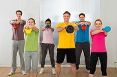 image of kettling  - Multiethnic Group Of People Lifting Kettle Bell Over White Background - JPG
