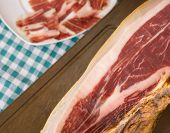 stock photo of shoulder-blade  - Serrano ham with plate and green tablecloth in the background - JPG