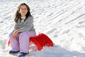 pic of sled  - pretty girl plays with the Red sled on the snow in the winter in the mountains - JPG