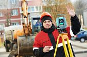 image of theodolite  - surveyor worker working with theodolite transit equipment at road construction site outdoors - JPG