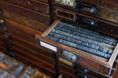 pic of armoire  - Old vintage metal printing press letters in a drawer - JPG