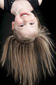 image of upside  - Happy little girl hanging upside down isolated on black - JPG