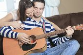 image of serenade  - A Handsome man serenading his girlfriend with guitar at home in the living room - JPG