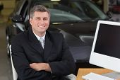 image of showrooms  - Smiling businessman sitting at his desk with arms crossed at new car showroom - JPG