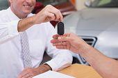 image of showrooms  - Smiling salesman giving a customer car keys at new car showroom - JPG