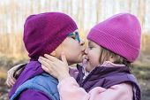 stock photo of three sisters  - older sister lovingly kissing her younger sister - JPG