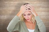 stock photo of confuse  - Confused young blonde with hands on head against wooden surface with planks - JPG