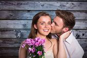 image of she-male  - Man kissing woman as she holds flowers against grey wooden planks - JPG