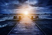 foto of storms  - Old wooden jetty during storm on the ocean - JPG