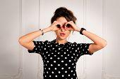 pic of binoculars  - Portrait of beautiful brunette woman in a black dress looking through her hands like binocular - JPG