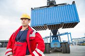 picture of shipyard  - Confident male worker standing in front of freight vehicle at shipyard - JPG