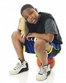 stock photo of preteen  - A preteen athlete looking distressed and wiping his brow as he sits on his basketball - JPG