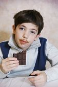 picture of preteen  - preteen handsome boy eat chokolate bar with dirty mouth  - JPG