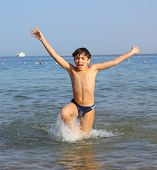stock photo of preteens  - preteen handsome boy swimming on the red sea beach and yaht background - JPG