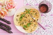 stock photo of purple rose  - Purple asparagus pancakes on a pink plate with roses - JPG