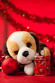 pic of christmas dog  - Toy dog with christmas ornaments over red - JPG