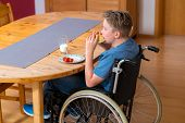 stock photo of bap  - disabled boy in wheelchair is eating in the living room - JPG