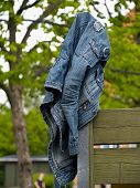 foto of denim jeans  - Blue jeans denim jacket hanged on a wooden fence - JPG