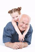 foto of granddaughters  - Portrait of a grandfather wearing blue checkered shirt and his small pretty granddaughter lying on his back and hugging smiling - JPG