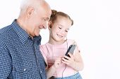 image of granddaughter  - Portrait of a small pretty granddaughter showing her grandfather wearing blue checkered shirt a smartphone while he is looking interested and smiling - JPG