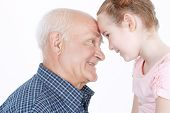 image of granddaughters  - Portrait of a grandfather wearing blue checkered and his small pretty granddaughter leaning their foreheads on each other smiling - JPG
