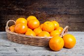 picture of valencia-orange  - still life of oranges on wicker and wood background - JPG