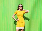 foto of green wall  - Fashion summer portrait of beautiful young woman in yellow dress and sunglasses against the colorful green wall - JPG
