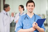 pic of doctors office  - Young male doctor with colleagues at doctor - JPG